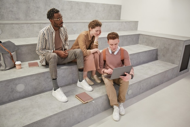 Hoge hoekmening bij groep studenten die samen laptop gebruiken en chatten in de moderne universiteitslounge, kopieer ruimte