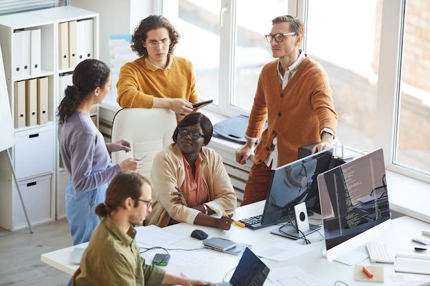 Hoge hoekmening bij multi-etnisch it-ontwikkelingsteam dat samenwerkt aan een zakelijk project tijdens het werken in de softwareproductiestudio