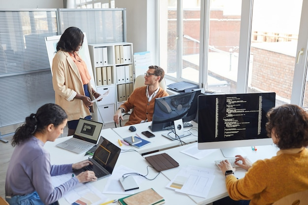 Hoge hoekmening bij multi-etnisch softwareontwikkelingsteam dat computers gebruikt en code schrijft terwijl ze samenwerkt aan een project in een modern kantoor, kopieer ruimte