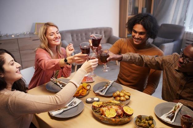 Hoge hoekmening bij multi-etnische groep gelukkige mensen roosteren terwijl u geniet van etentje met vrienden en familie