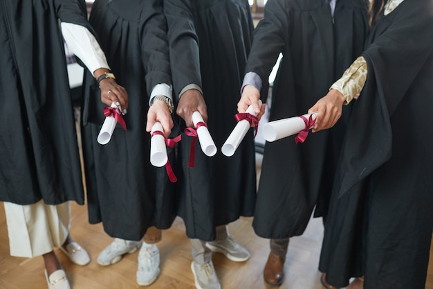 Hoge hoekmening bij multi-etnische groep jongeren die afstudeergewaden dragen en diploma's naar de camera richten
