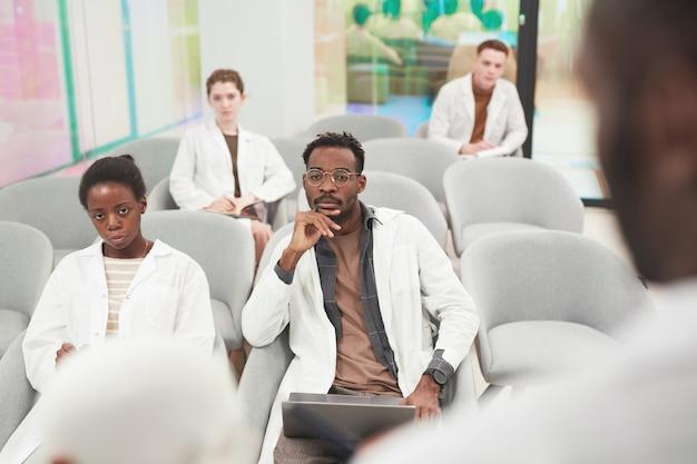 Hoge hoekmening bij multi-etnische groep mensen die laboratoriumjassen dragen terwijl ze luisteren naar een lezing over medicijnen op de universiteit of coworking center, kopieer ruimte