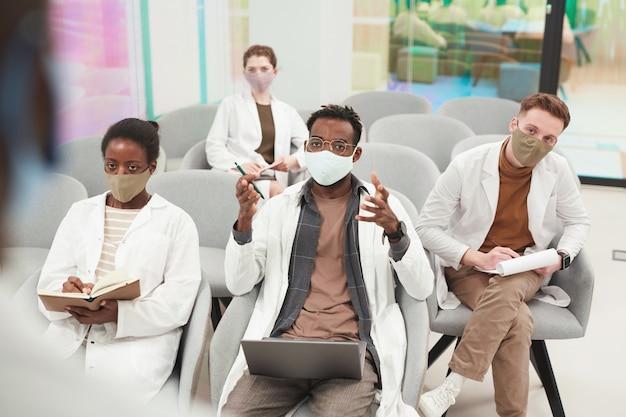 Hoge hoekmening bij multi-etnische groep mensen die maskers en laboratoriumjassen dragen terwijl ze luisteren naar een lezing over medicijnen op de universiteit of een coworkingcentrum, kopieer ruimte