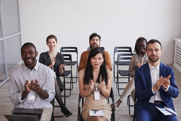 Hoge hoekmening bij multi-etnische groep mensen die naar de camera kijken en applaudisseren terwijl ze in het publiek zitten op een zakelijke conferentie of seminar, kopieer ruimte