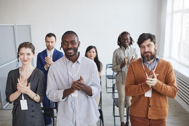Hoge hoekmening bij multi-etnische groep zakenmensen applaudisseren opstaan en glimlachen in publiek op zakelijke conferentie of seminar, kopieer ruimte