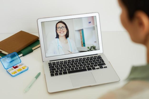Hoge hoekmening bij onherkenbare vrouw die praat met vrouwelijke arts op laptopscherm via videochat tijdens online consult, kopieer ruimte