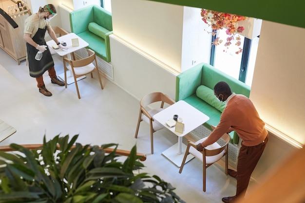 Hoge hoekmening bij twee cafémedewerkers die tafels schoonmaken en meubels ontsmetten terwijl ze zich voorbereiden op opening in de ochtend, kopieer ruimte