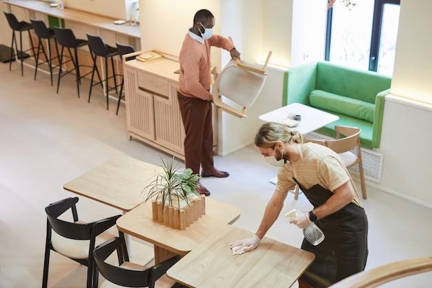 Hoge hoekmening bij twee mensen die tafels in café schoonmaken terwijl ze zich voorbereiden op opening in de ochtend, kopieer ruimte
