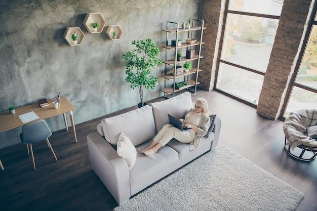 Hoge hoekmening foto van blonde leeftijd oma met behulp van laptop lezen kleinkinderen e-mail typen antwoord liggend sofa divan woonkamer ruime appartementen binnenshuis