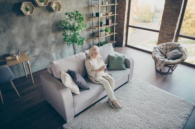 Hoge hoekmening foto van verbazingwekkende blonde schattige oude oma goed humeur met behulp van telefoon kleinkinderen e-mail lezen moderne gebruiker zit comfortabele bank divan woonkamer binnenshuis