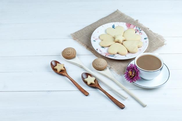 Hoge hoekmening hartvormige koekjes op stuk zak met bloem, koekjes in houten lepels, kopje koffie op witte houten plank achtergrond. horizontaal