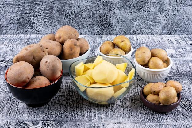 Hoge hoekmening kleine, gehakte en grote aardappelen in kommen op grijze houten tafel
