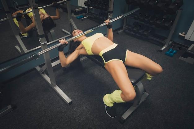 Hoge hoekmening naar aantrekkelijke vrouwelijke carrosseriebouwer in gele en zwarte outfit liggend op de bank en duwend gewicht op de achtergrond van de gymzaal. leuk meisje dat perfect lichaam bouwt in sportclub. fitnessapparatuur.