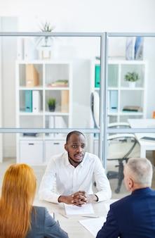 Hoge hoekmening op hedendaagse afro-amerikaanse man beantwoorden van vragen aan hr-manager tijdens sollicitatiegesprek in kantoor, kopie ruimte