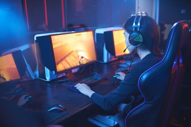 Hoge hoekmening op jonge aziatische man spelen van videogames en het dragen van koptelefoon in donkere cyber sport interieur, kopie ruimte