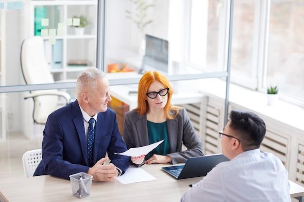 Hoge hoekmening op twee managers interviewen jonge man voor baan op kantoor, kopieer ruimte