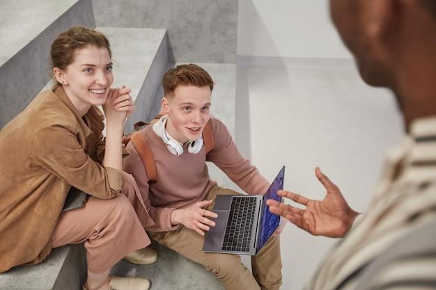 Hoge hoekmening op vrolijke groep studenten die tijdens de pauze chatten en laptop gebruiken in de schoollounge