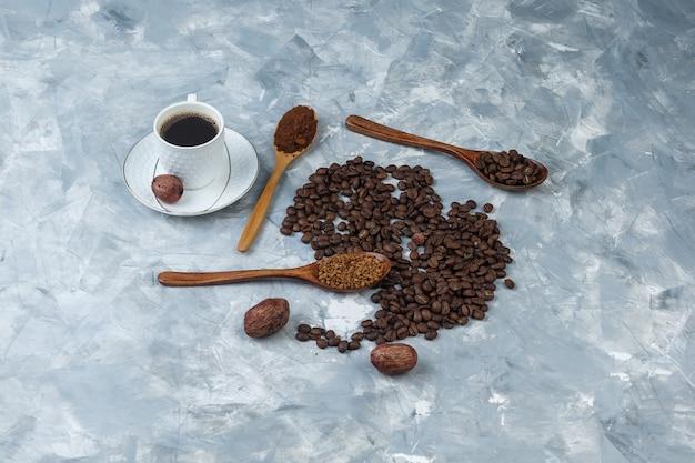 Hoge hoekmening oploskoffie, koffiemeel, koffiebonen in houten lepels met kopje koffie, koekjes op lichtblauwe marmeren achtergrond. horizontaal