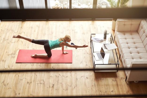 Hoge hoekmening van actieve volwassen vrouw in sportkleding die oefeningen doet op een mat thuis voor