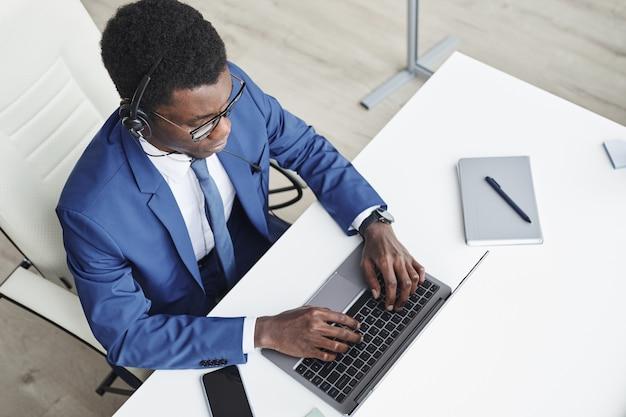 Hoge hoekmening van afrikaanse zakenman in koptelefoon typen op laptop en online communiceren op zijn werkplek op kantoor