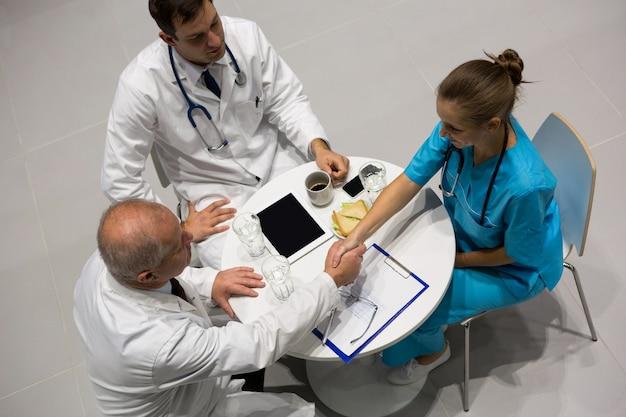 Hoge hoekmening van artsen en chirurg die handen schudden