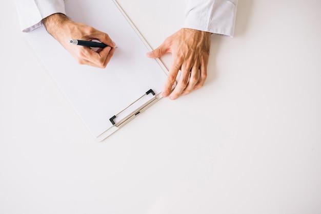 Hoge hoekmening van artsenhand die op leeg witboek schrijft