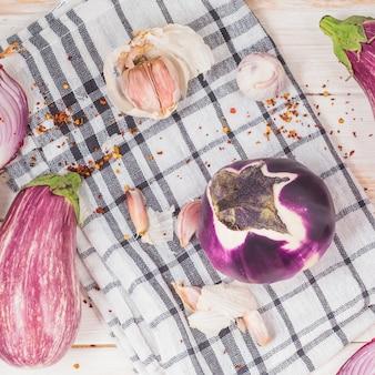 Hoge hoekmening van aubergines; ui en knoflookteentjes op geruit patroondoek