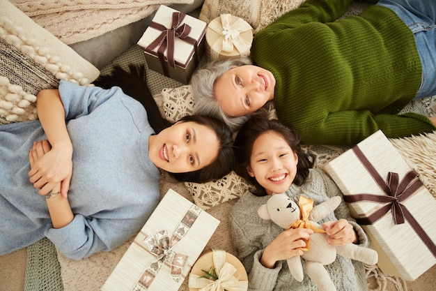 Hoge hoekmening van aziatische familie generatie liggend op de vloer onder cadeautjes en speelgoed en glimlachen