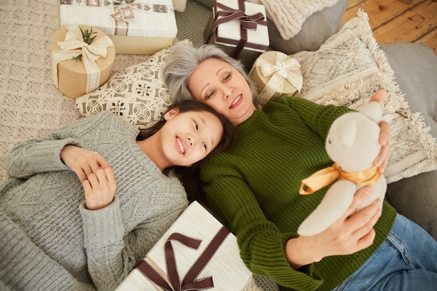 Hoge hoekmening van aziatische grootmoeder spelen met speelgoed samen met haar kleindochter op de vloer thuis