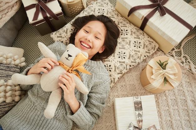 Hoge hoekmening van aziatische meisje liggend op de vloer met speelgoed en glimlachen