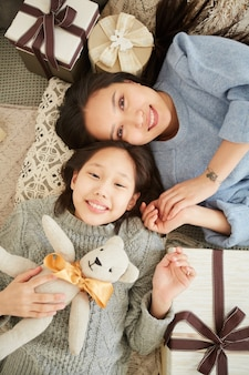 Hoge hoekmening van aziatische moeder speelt met haar dochter met speelgoed liggend op de vloer thuis