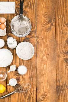 Hoge hoekmening van bakken gebruiksvoorwerpen en ingrediënten voor het voorbereiden van cookies gerangschikt op houten tafel