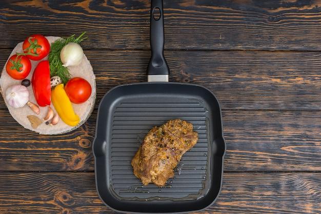 Hoge hoekmening van bereid vlees op een grillpan naast groenten op houten bureau