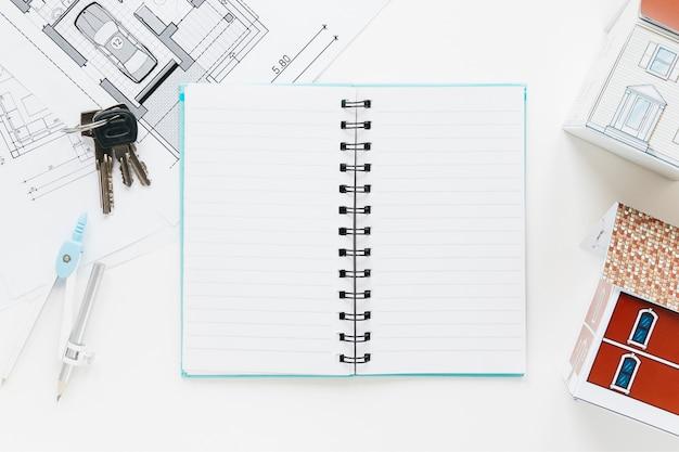 Hoge hoekmening van blauwdruk; toetsen; open dagboek met huismodel
