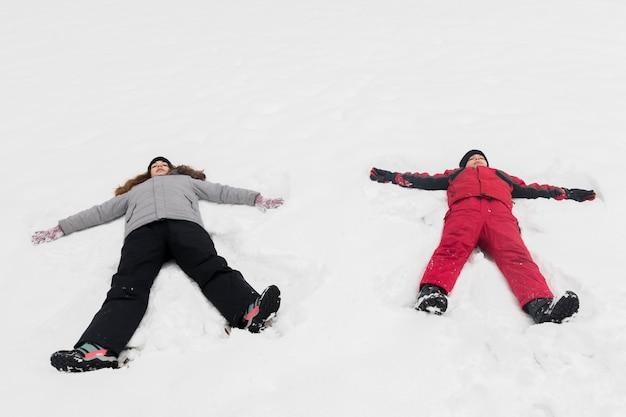 Hoge hoekmening van broer en zuster die op sneeuw liggen
