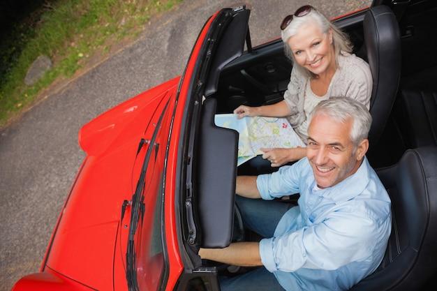Hoge hoekmening van de glimlachende rijpe mens die een rit met zijn vrouw heeft