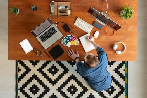 Hoge hoekmening van de mens in denimoverhemd die zich bij bureau bevinden en ui-ontwerpschets maken in kladblok