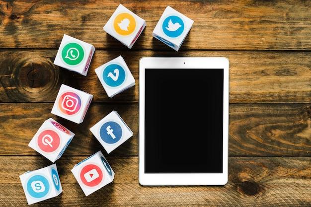 Hoge hoekmening van digitale tablet in de buurt van vakken met media iconen