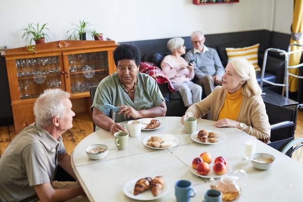 Hoge hoekmening van diverse groep senioren die genieten van ontbijt in een gezellige kopieerruimte voor verpleeghuizen