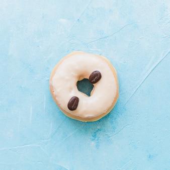 Hoge hoekmening van donuts versierd met koffiebonen op blauwe achtergrond