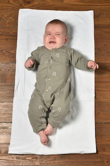 Hoge hoekmening van een baby op de parketvloer gekleed, huilend en kijkend naar de camera