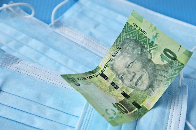 Hoge hoekmening van een bankbiljet op sommige chirurgische maskers op een blauw oppervlak