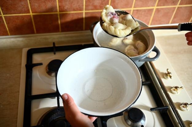 Hoge hoekmening van een banketbakker haalt gekookte knoedels uit kokend water in een vergiet. detailopname