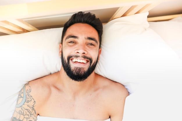 Hoge hoekmening van een glimlachende mens die op bed ligt