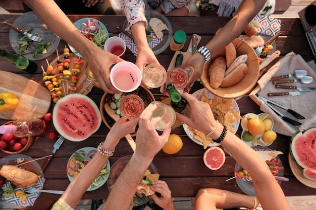 Hoge hoekmening van een groep vrienden die met wijn en bier roosteren terwijl ze buiten een picknick hebben