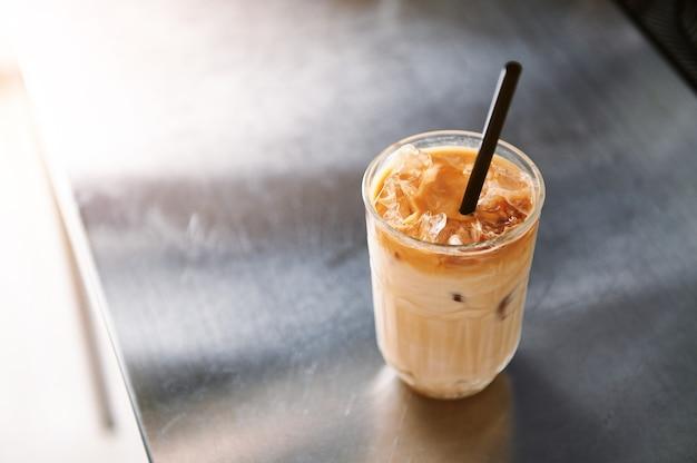Hoge hoekmening van een ijskoffie latte met stro op een stalen aanrechtblad in koffiehuis. verfrissende en verkwikkende cafeïnehoudende dranken op warme zomerdagen