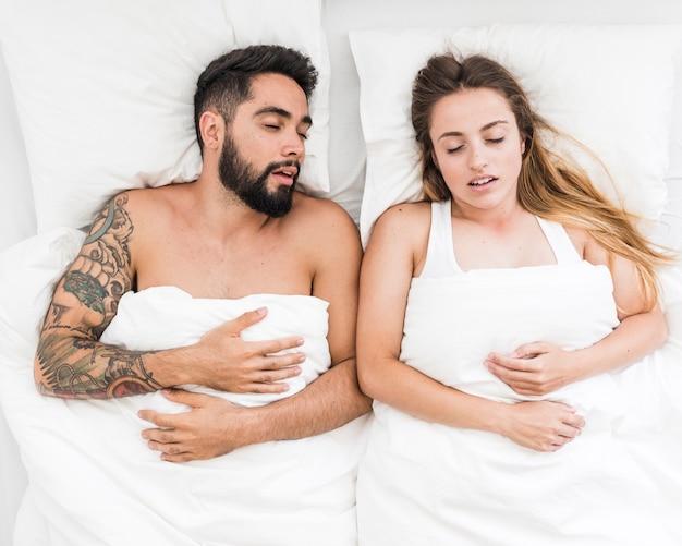 Hoge hoekmening van een jong koppel slapen op bed
