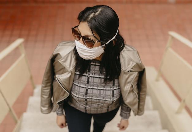 Hoge hoekmening van een jonge spaanse vrouw met een zonnebril die een gezichtsmasker draagt