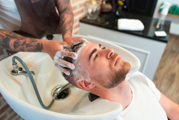 Hoge hoekmening van een kapper met tatoeages die het haar wassen van een jonge mannelijke klant