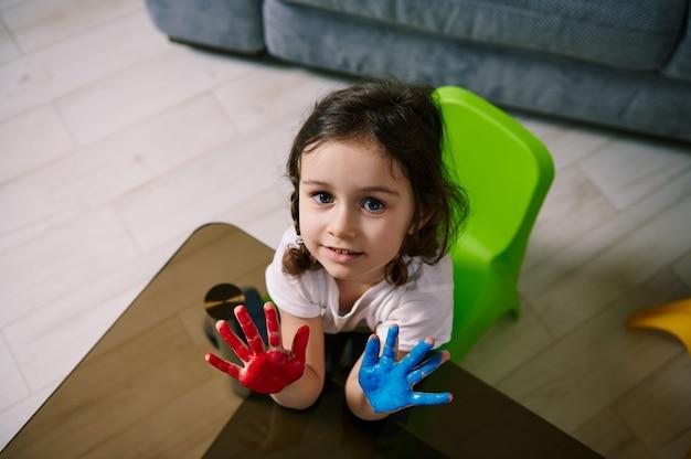 Hoge hoekmening van een klein meisje met geschilderde handen kijken naar de camera, zittend aan een glazen tafel